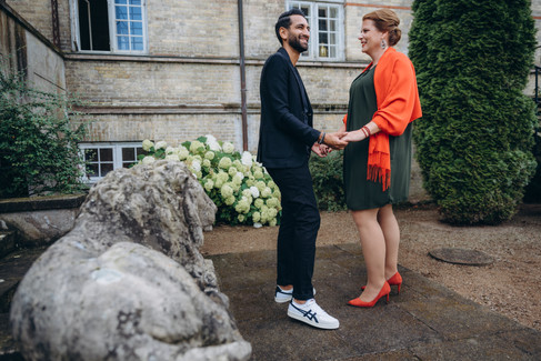Man and wife holding hands in a romantic courtyard, surrounded by flowers and stone sculptures while they renew wedding vows, a great location if you are interested in getting married abroad.