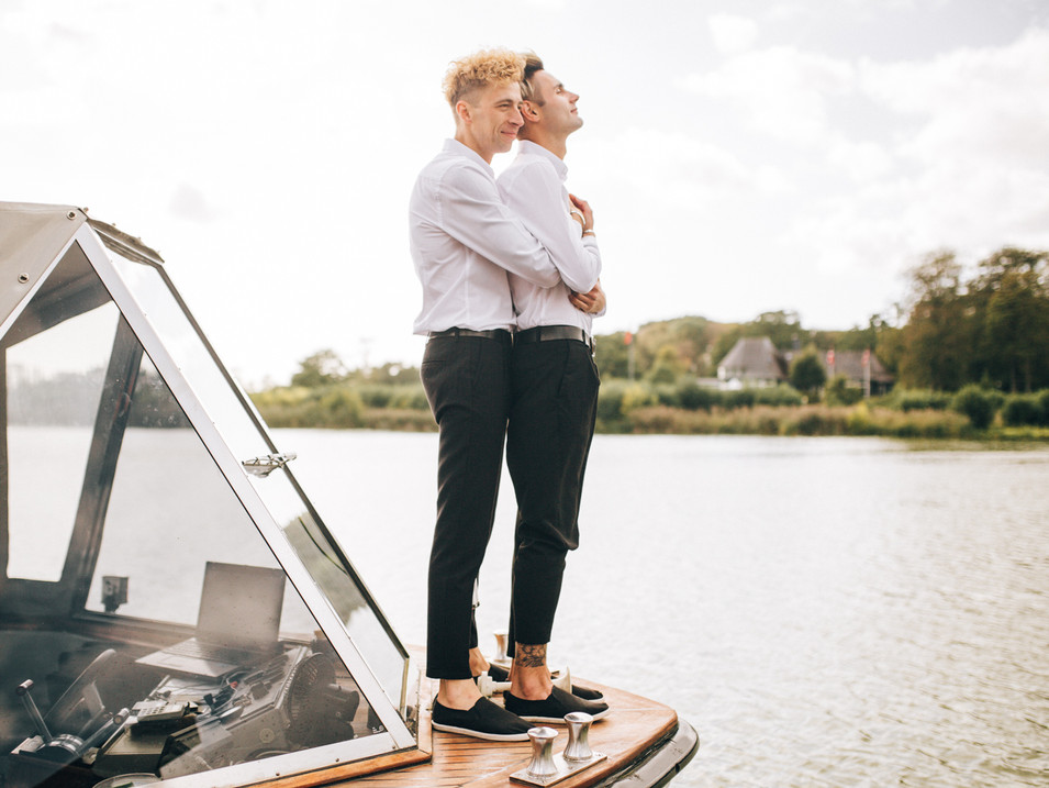 a same-sex couple embracing each other on the boat deck during their small intimate wedding abroad in Denmark.