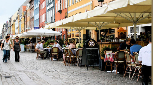 A fiew to the Nyhavn street with many cafe and people sitting outdoor.