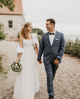 Newlyweds holding hands after their wedding ceremony at Stevens Klint in Denmark, one of the best destinations for a Nordic wedding abroad.