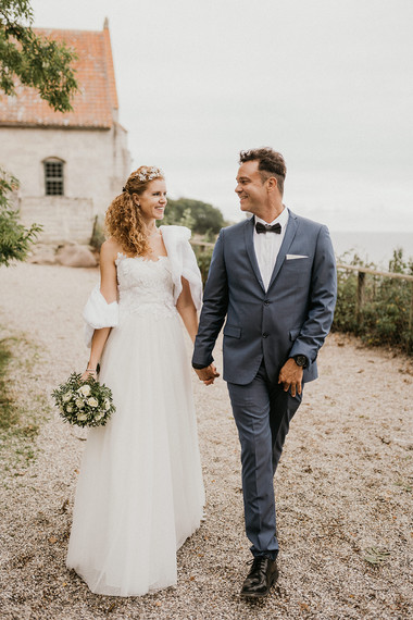 A  wife and groom walking by the romantic Stevens Klint cliffside during their Nordic wedding in Denmark, a lovely marry abroad idea for couples that want an intimate destination wedding.