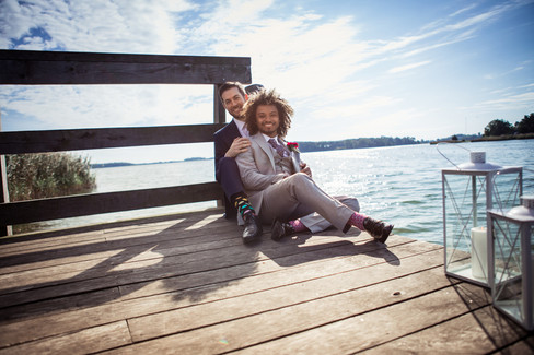 A gay couple sitting by the lake and smiling during their gay marriage in Denmark