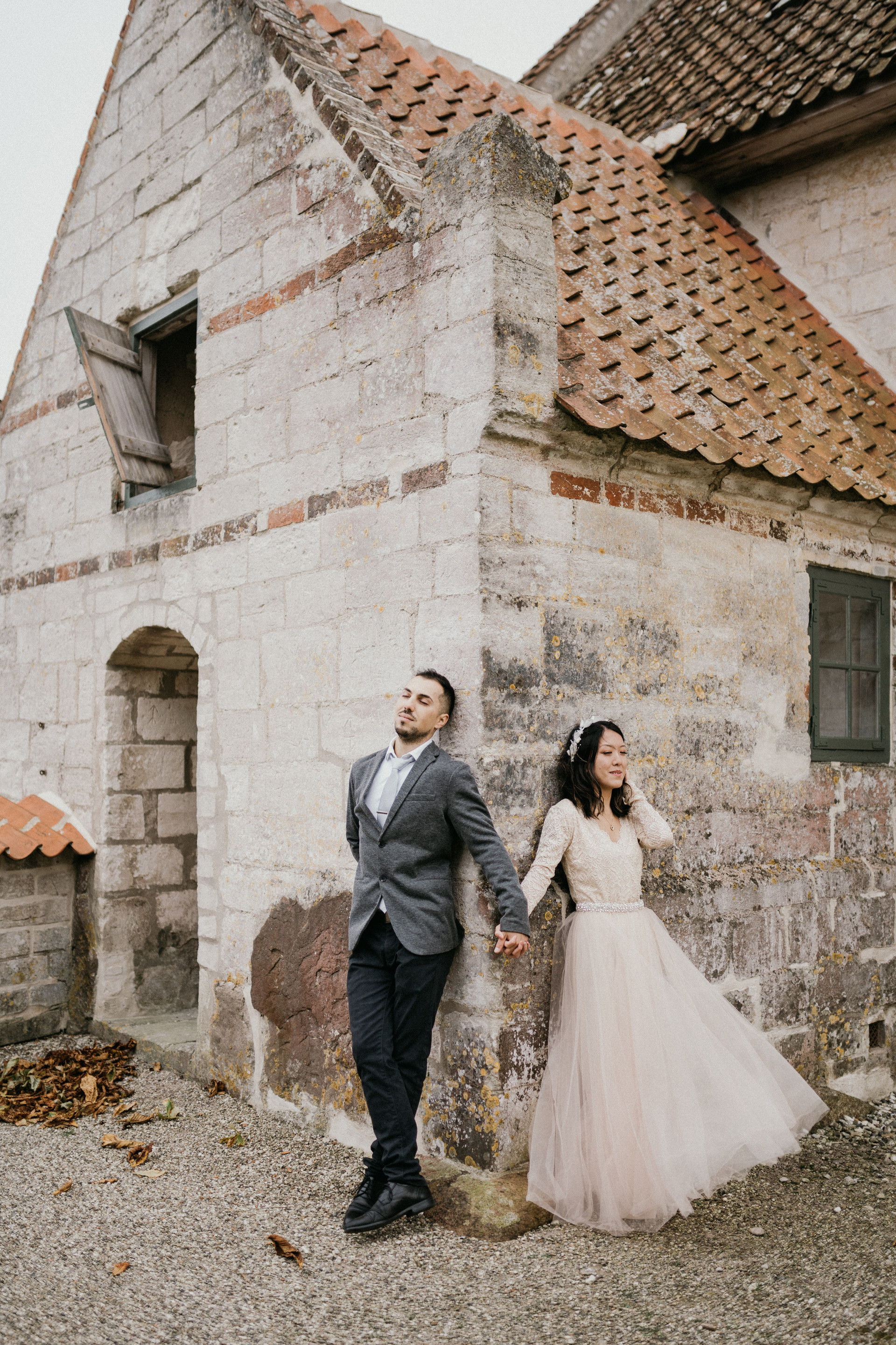 A couple posing at the Old Hojerup Church during their elopement abroad, one of Denmark's best destination wedding locations.