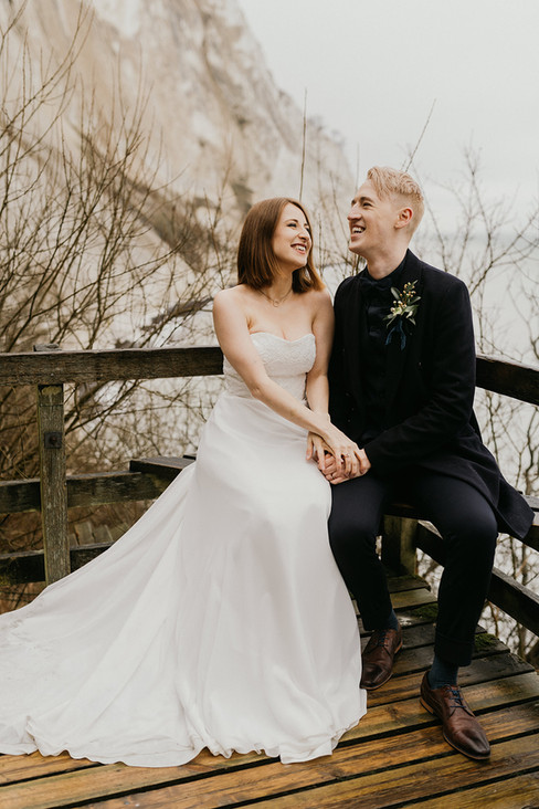 Newlyweds laughing and holding hands at Mons Klint as they enjoy their winter elopement after booking our popular Denmark elopement package.