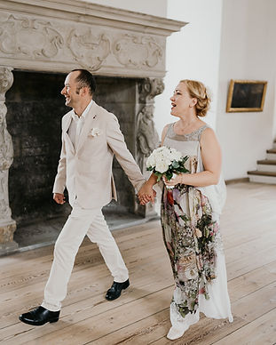 Newlyweds holding hands and walking through Hamlet's Elsinore Castle during their Denmark elopement, made possible by our wedding packages abroad for two.