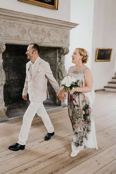 Newlyweds holding hands and walking through Hamlet's  Elsinore castle as they enjoy getting married in Denmark