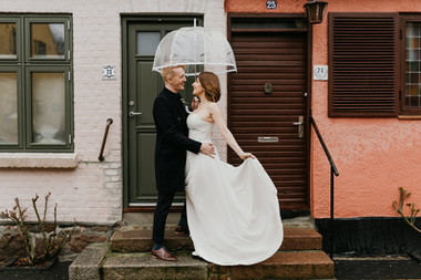 Husband and wife sharing an umbrella as they get married in Denmark