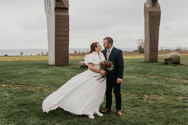 A romantic moment between husband and wife as they gaze into each other's eyes at the Dodecalith in Lolland Island during their adventure elopement in Denmark