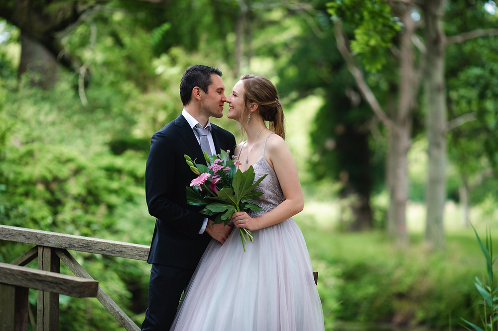 the couple touches each other with their noses and the bride holds a simple wedding bouquet of chrysanthemums