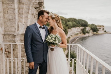 Newlyweds laughing and being close to each other outside of the historic ancient church in Denmark, one of the most romantic and best places to get married abroad.