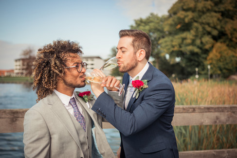 A couple interlacing arms and drinking champagne during their first newlywed toast by the lake, their dream gay elopement in Denmark.