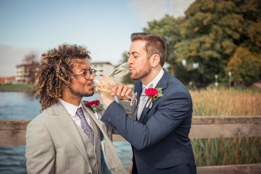 A gay couple drinking champagne on Maribo Lake toasting to their love and Denmark's same-sex marriage laws.
