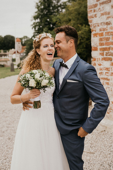 A couple smiling in front of the ancient church, a top Denmark wedding venue for couples dreaming of a Nordic wedding.