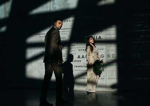 A photograph of a couple standing in angular shadows while they renew wedding vows in an urban building, a stunning but simple venue for Denmark weddings as well.