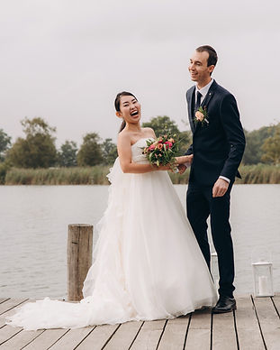 A couple rejoicing during their eco-style wedding in Denmark by the lake.