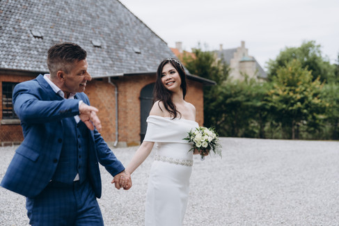 Newlyweds holding hands and walking through nature during their Danish wedding adventure.