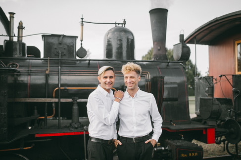Two grooms standing in front of an old train during their gay marriage in Denmark.