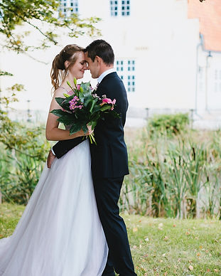 Husband and wife embracing during their adventure elopement to Denmark at a castle courtyard, one of our options for wedding packages abroad for two.