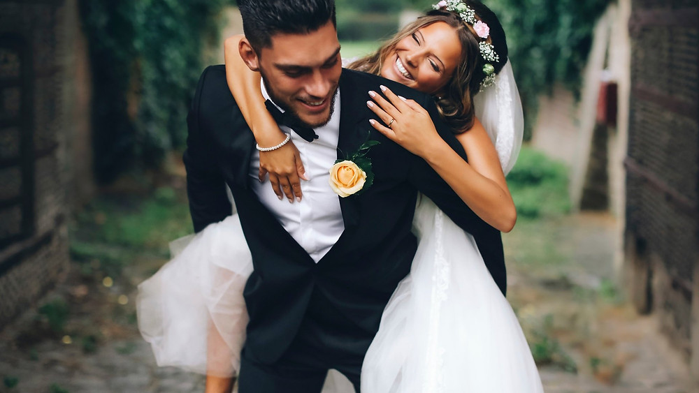 A groom drags the bride on his back during their adventure elopement in Denmark