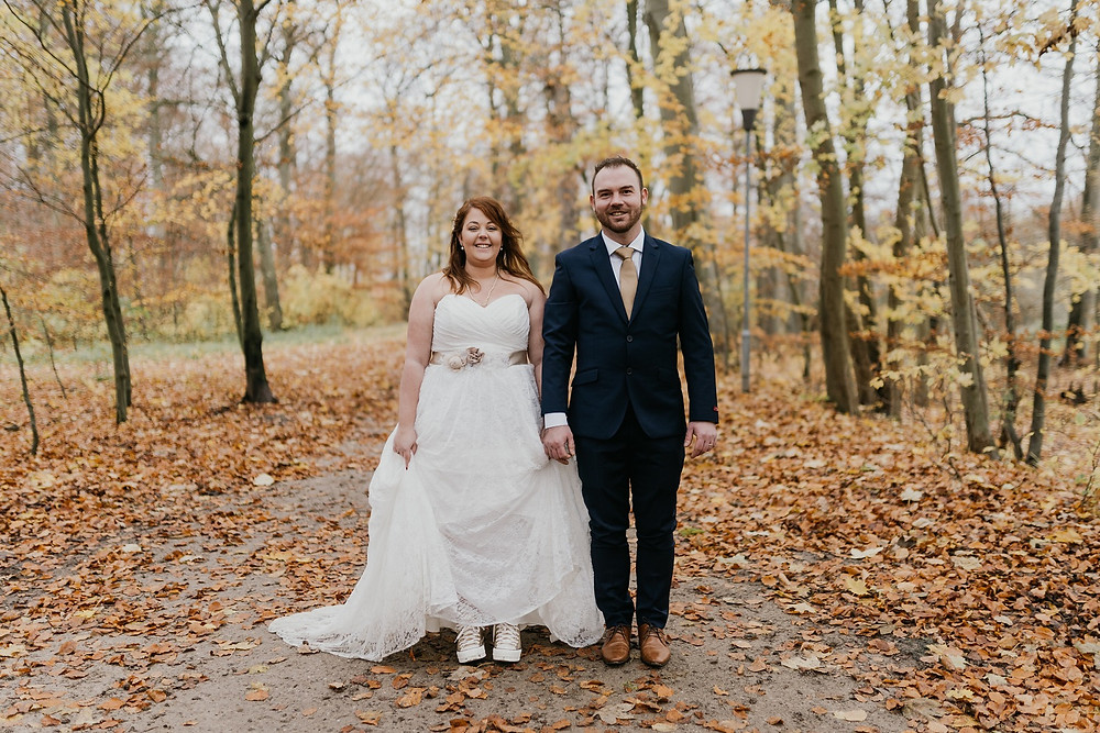 bride-and-groom-stand-on-a-road-strewn-with-autumn-leaves