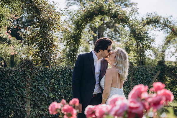 A couple kissing passionately at a rose garden, an ideal romantic wedding venue abroad.