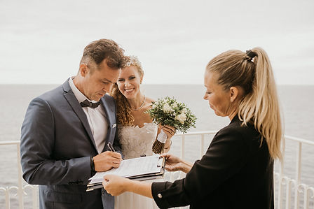 A couple signing paperwork during their civil wedding abroad at the ancient Hojerup Church's balcony with a sea-view, a truly unique destination wedding location.