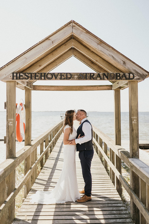 Newlyweds kissing at the Hestehoved Jetty in Denmark during their overseas wedding at Lolland Island.