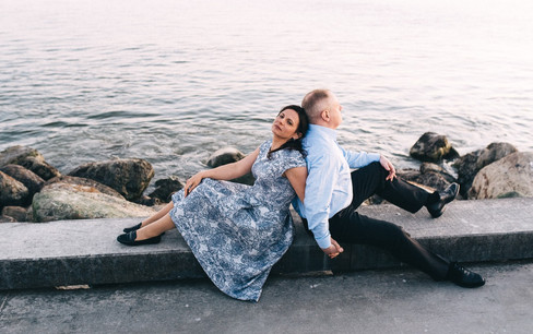 A married couple sitting back-to-back on the pier by the seashore, intimately celebrating their renewal of vows abroad.