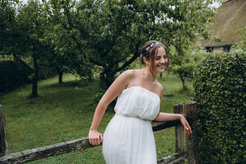 A bride leaning on a picket fence and smiling in the midst of her country wedding at a very green Denmark wedding venue.