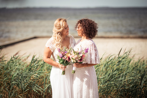 Two brides looking into each others eyes and smiling during their gay marriage in Denmark, a great destination for same-sex weddings abroad.