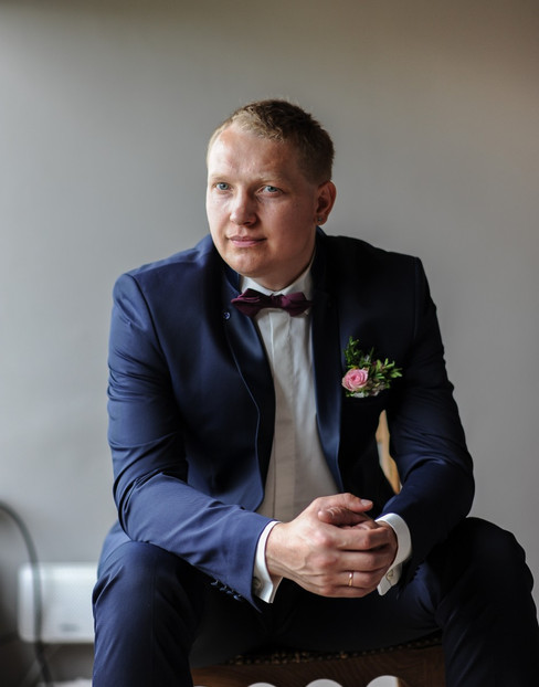 A portrait of a groom sitting and waiting for his bride during their Scandinavian wedding in Denmark, one of the best places for an overseas wedding.