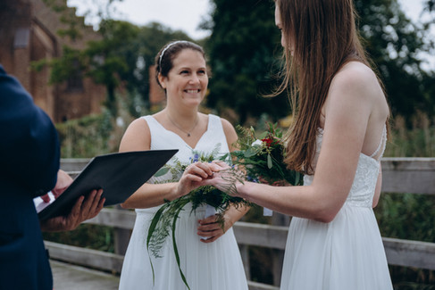 A bride putting a ring on her bride by the Maribo Lake in Lolland Island as they get married in Denmark.