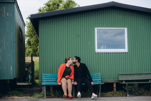 Kissing on a blue bench in front of a green-colored house, this couple enjoys picturesque Denmark making their vow renewal idea come true.