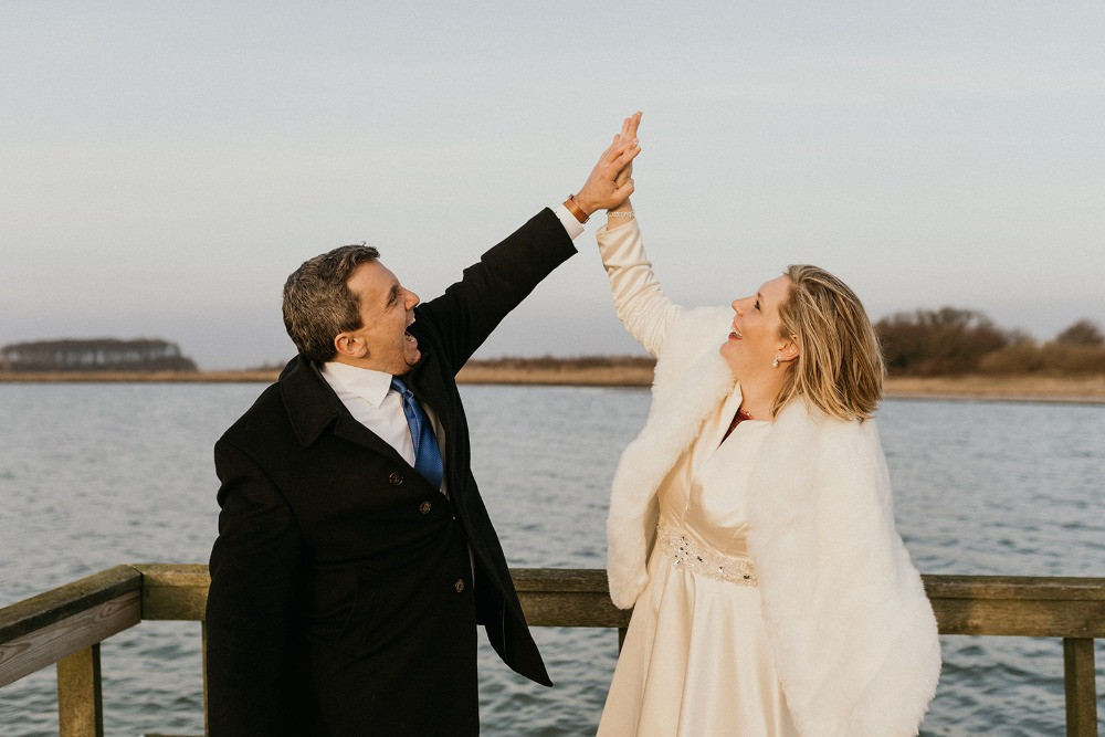Happy couple are posing at the breech since they getting married in Denmark simple and easy