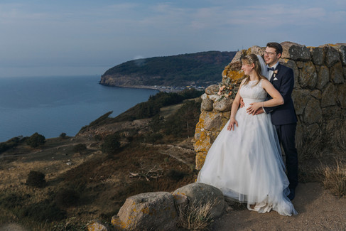 Newlyweds embracing and looking out at the Baltic Sea from the Hammershus Ruins on Bornholm Island, while getting married in Denmark