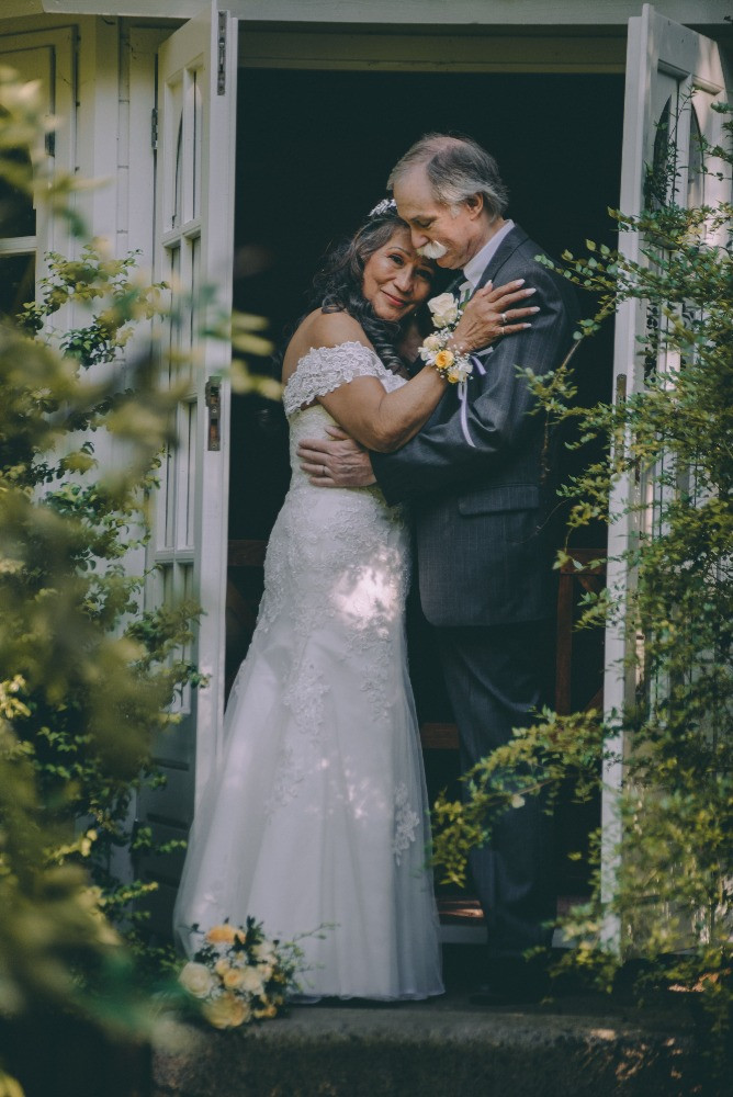 A senior groom holds his bride and enjoying time of their elopement abroad