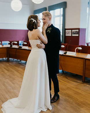 Newlyweds happily looking into each other's eyes and embracing warmly during their town hall ceremony, a practical Denmark wedding venue for couples of all nationalities.