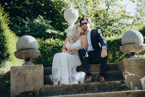 The bride kissing her groom on the cheek as they sit on stone steps in the romantic Denmark wedding venue they selected as a part of our wedding packages abroad for two.