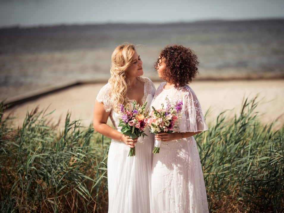 A couple looking into each other eyes on a Nordic beach during their lesbian wedding in Denmark, a country with liberal same-sex marriage laws.