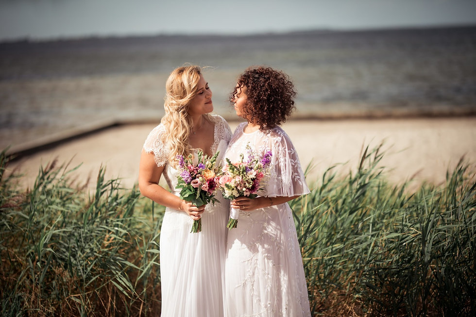 Brides looking into each other's eyes as they enjoy their lesbian wedding on the beach in Denmark.