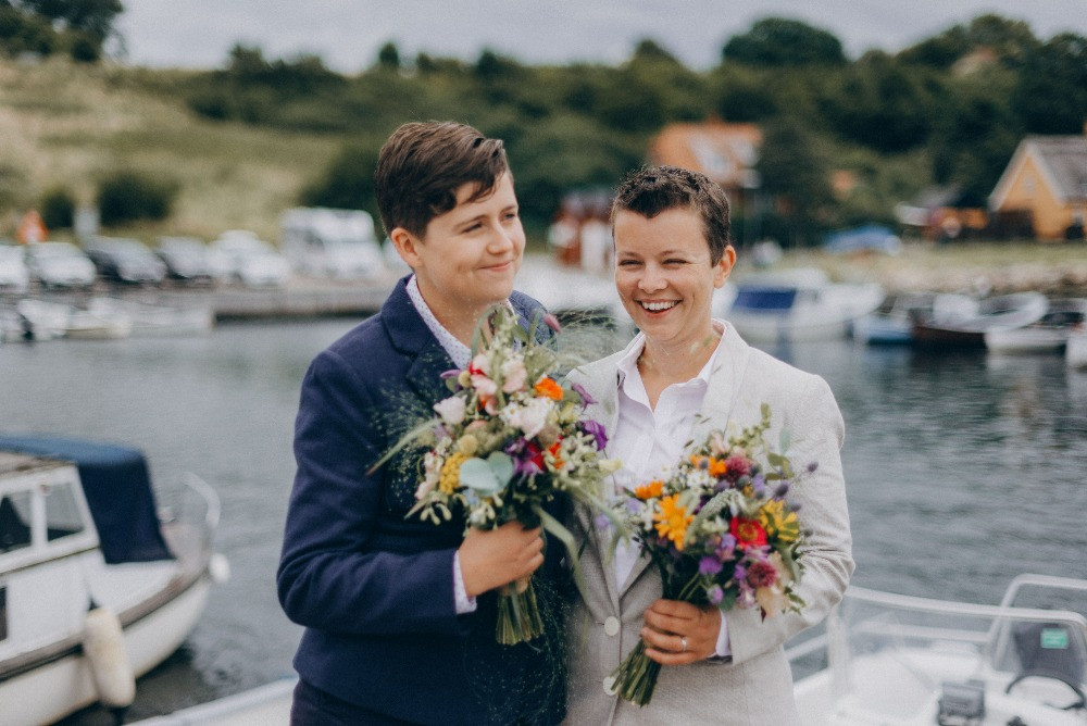 LGBT couple posing in the harbour after their same sex wedding in Denmark