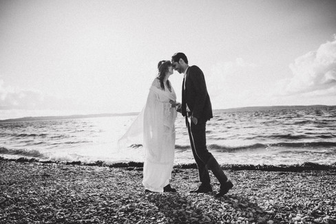 A couple romantically embracing by the beach during their Danish wedding in Denmark, one of the best places to elope.