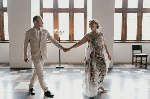 Husband and wife holding hands as they stroll through Hamlet's Elsinore Castle, as they have fun getting married in Denmark.