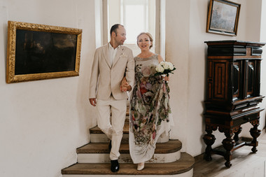 Husband and wife walking down the stairs in Hamlet's Elsinore Castle for their destination wedding adventure in Denmark.