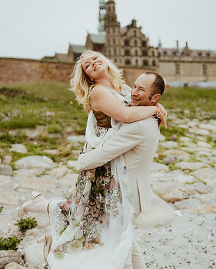 A groom lifting his bride off the ground in smiles as they pose in front of Hamlet's Elsinore Castle for their castle wedding portraits.