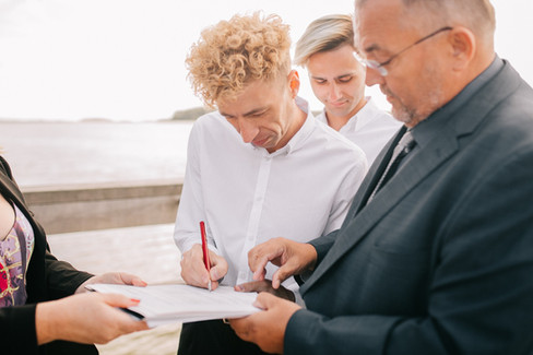 A groom signing paperwork during his outdoor gay marriage ceremony in Denmark.
