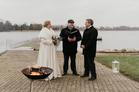 Newlyweds during their Lolland Island wedding ceremony by the fire, a perfect winter elopement to Denmark.