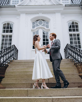 A couple standing in front of the Vindeholme Castle and holding hands, enjoying their castle wedding venue.