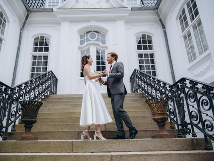 A couple on the steps of the Vindeholme Castle, enjoying their small castle wedding.