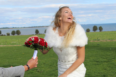 A wife laughing as she receives a bouquet of roses during her Lolland Island adventure wedding in Denmark.